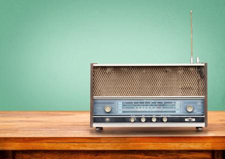 Foto de Old retro radio on table with vintage green eye light background - Imagen libre de derechos