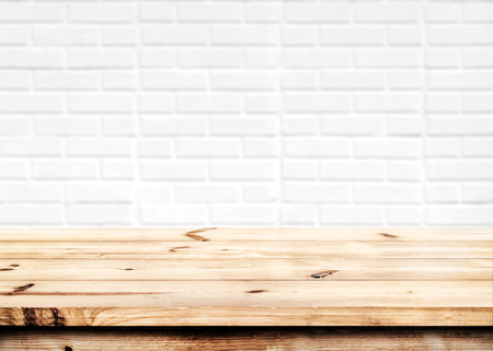 Foto de Empty wooden table for product placement or montage with focus to the table top in the foreground, with white brick wall background. - Imagen libre de derechos