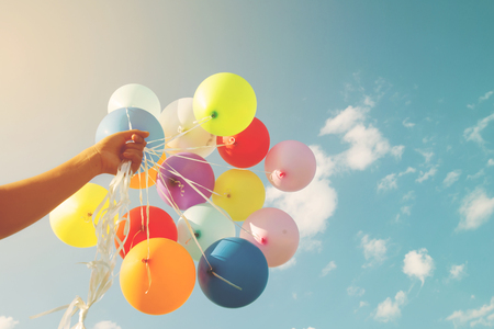 Photo pour Girl hand holding multicolor balloons done with a retro  filter effect, concept of happy birth day in summer and wedding honeymoon party (Vintage color tone) - image libre de droit