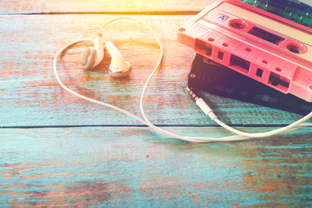 Photo for Top view (above) shot of retro tape cassette with earphone heart shape on wood table. Love music concept - vintage color effect styles - Royalty Free Image