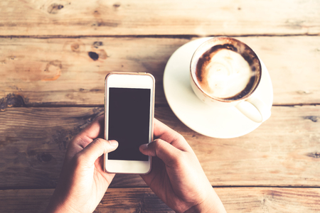 Photo pour Close up of beautiful young hipster woman's hands holding mobile smart phone with hot coffee cup at cafe shop, female using cell telephone with blank copy space screen for your advertising text message. vintage color tone - image libre de droit