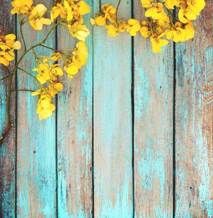 Foto de Yellow flowers on vintage wooden background, border design. vintage color tone - concept flower of spring or summer background - Imagen libre de derechos
