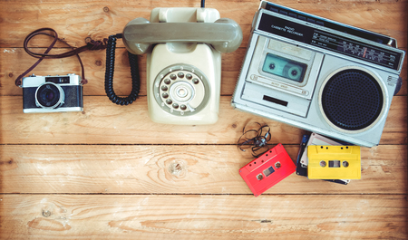 Photo pour Top view hero header - retro technology of radio cassette recorder with retro tape cassette, vintage telephone and film camera on wood table. Vintage color effect styles. - image libre de droit
