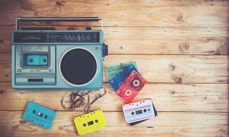 Photo pour Top view hero header - retro technology of radio cassette recorder music with retro tape cassette on wood table. Vintage color effect styles. - image libre de droit