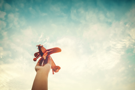 Photo pour Childhood inspiration - Hands of children holding a toy plane and have dreams wants to be a pilot - Vintage filter effect - image libre de droit
