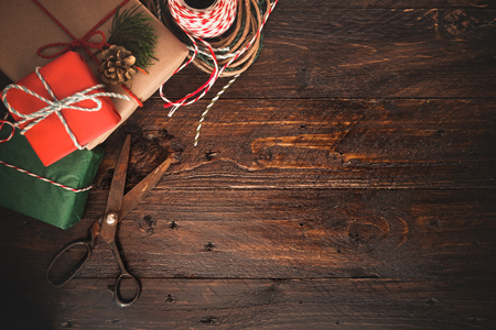 Foto de Christmas presents wrapping over wooden table background with copy space. Gift wrapping for Christmas and New Year. Handmade. - Imagen libre de derechos