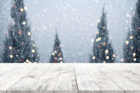 Photo for Christmas and New year background with wooden deck table over christmas tree, snow and blurred light bokeh. Empty display for product montage. Rustic vintage Xmas background. - Royalty Free Image