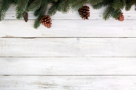 Foto de Christmas background - fir leaves and pine cones decorating rustic elements on white wood table. Creative Flat layout and top view composition with border and copy space design. - Imagen libre de derechos