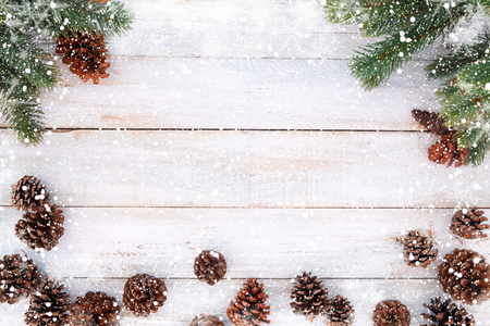 Foto de Christmas background - fir tree and pine cones decorating rustic elements on white wood table with snowflake. Creative Flat layout and top view composition with border and copy space design. - Imagen libre de derechos