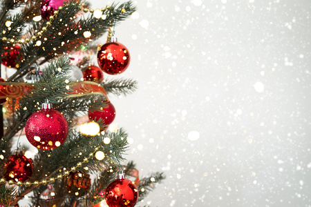 Photo for Close-up of Christmas tree with ornament, decoration and light bokeh with snowfall on winter background - Royalty Free Image