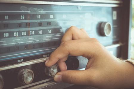 Foto de Retro lifestyle - Woman hand adjusting the button vintage radio receiver for listen music or news - vintage color tone effect. - Imagen libre de derechos