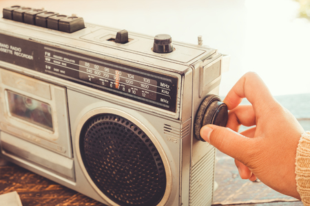 Photo pour Retro lifestyle - Woman's hand switched and adjusting button cassette player and recorder for listen music - vintage color tone effect. - image libre de droit