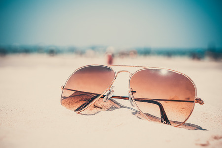 Photo pour Vintage photo of nostalgia in summer - sunglasses on sand beach. retro film filter effect - image libre de droit
