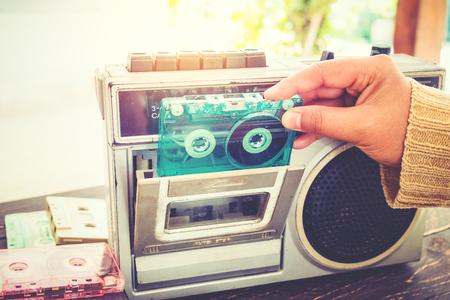 Foto de Retro lifestyle - Woman hand holding tape cassette with cassette player and recorder for listen music - vintage color tone effect. - Imagen libre de derechos