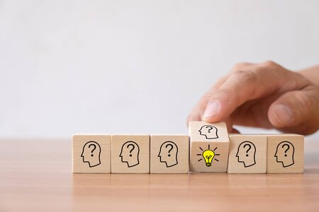 Photo pour Business concept of creative idea and innovation. Hand flip over wooden cube block with light bulb icon (new idea) and head human symbol have no idea. - image libre de droit