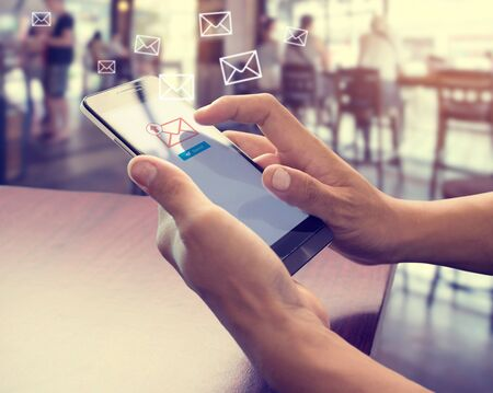 Foto de Hand of male using mobile phone to sending E-mail message with email symbol and envelope icon. Email marketing concept - Imagen libre de derechos