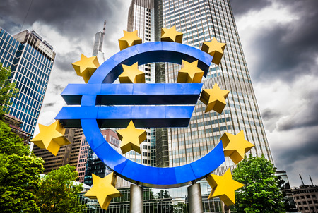 Photo for Euro sign at European Central Bank headquarters in Frankfurt, Germany with dark dramatic clouds symbolizing a financial crisis - Royalty Free Image