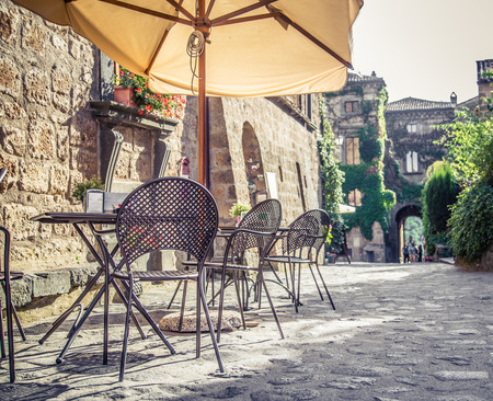Photo for Cafe with tables and chairs in an old street in Europe with retro vintage style filter effect - Royalty Free Image