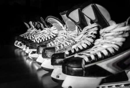 Photo for Pairs of hockey skates lined up in a locker room - Royalty Free Image