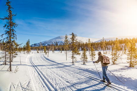 Photo pour Panoramic view of male person cross-country skiing in Scandinavia in golden evening light at sunset - image libre de droit