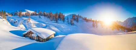 Photo pour Panoramic view of beautiful winter mountain landscape with snow capped mountain cabin in the Alps in golden evening light at sunset - image libre de droit