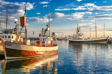 Photo pour Panoramic view of traditional old wooden fisherman boats lying in harbor in beautiful golden evening light at sunset, town of Husavik, Skjalfandi Bay, Iceland, northern Europe - image libre de droit