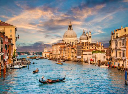 Foto de Beautiful view of traditional Gondola on famous Grand Canal with Basilica di Santa Maria della Salute in golden evening light at sunset in Venice, Italy - Imagen libre de derechos