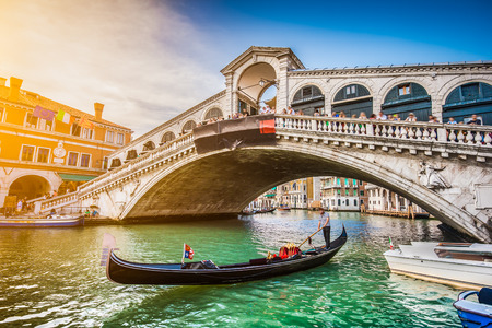 Foto de Beautiful view of traditional Gondola on famous Canal Grande with Rialto Bridge at sunset in Venice, Italy   - Imagen libre de derechos