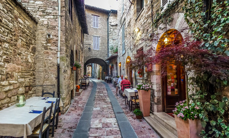 Photo for Romantic dinner place in a beautiful alley in the ancient town of Assisi, Umbria, Italy - Royalty Free Image