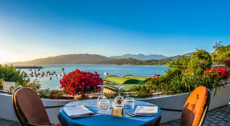 Foto de Romantic dinner place with idyllic panoramic view of mediterranean coastal landscape at sunset in golden evening light - Imagen libre de derechos