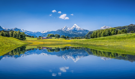 Foto de Panoramic view of idyllic summer landscape in the Alps with clear mountain lake and fresh green mountain pastures in the background - Imagen libre de derechos