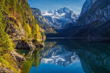 Foto de Beautiful view of idyllic colorful autumn scenery with Dachstein mountain summit reflecting in crystal clear Gosausee mountain lake in fall, Salzkammergut region, Upper Austria, Austria - Imagen libre de derechos