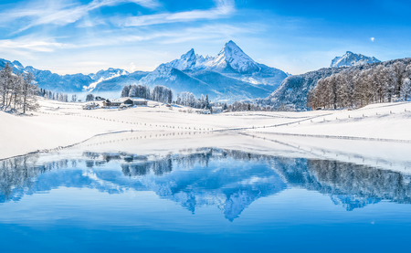 Photo pour Winter wonderland scenery in the Alps with snowy mountain summits reflecting in crystal clear mountain lake on a cold sunny day with blue sky and clouds - image libre de droit