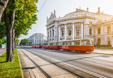 Foto de Famous Wiener Ringstrasse with historic Burgtheater and traditional red electric tram at sunrise with retro vintage style filter effect in Vienna, Austria - Imagen libre de derechos