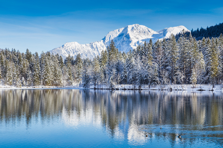 Foto de Idyllic winter wonderland with crystal clear mountain lake in the Alps on a cold sunny day - Imagen libre de derechos