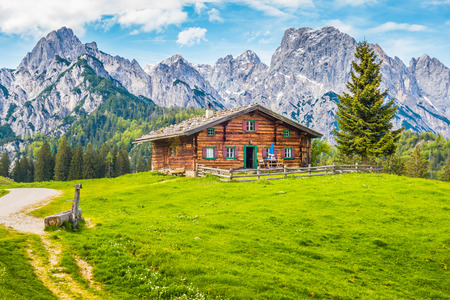 Photo pour Panoramic view of scenic mountain landscape in the Alps with traditional old mountain chalet and fresh green meadows on a sunny day with blue sky and clouds in spring - image libre de droit