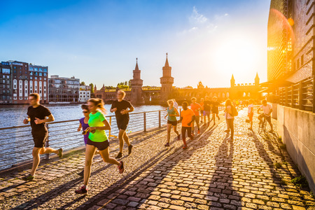 Photo pour Group of female and male young runners jogging outside in golden evening light at sunset in summer with retro vintage style toned filter and lens flare sunlight effect in the background - image libre de droit