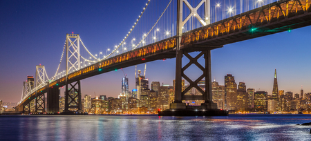 Foto de Classic panoramic view of famous Oakland Bay Bridge with the skyline of San Francisco illuminated in beautiful twilight after sunset in summer, California, USA - Imagen libre de derechos