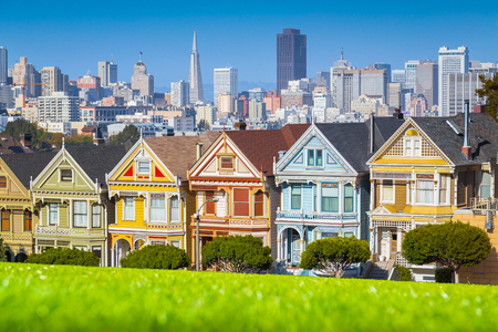 Photo pour Classic postcard view of famous Painted Ladies, a row of colorful Victorian houses located at scenic Alamo Square, with the skyline of San Francisco in the background on a beautiful sunny day with blue sky in summer - image libre de droit