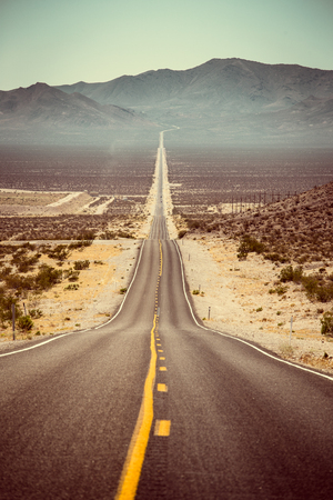 Foto de Classic panorama view of an endless straight road running through the barren scenery of the American Southwest with extreme heat haze on a beautiful hot sunny day with blue sky in summer - Imagen libre de derechos