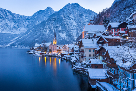 Foto de Classic postcard view of famous Hallstatt lakeside town in the Alps with beautiful Hallstattersee in mystical post sunset twilight during blue hour at dusk in winter, Salzkammergut, Austria - Imagen libre de derechos