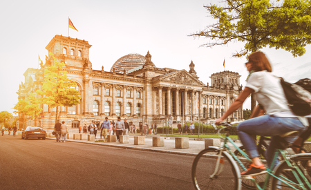 Photo for Urban city life with famous Reichstag building in the background in beautiful golden evening light at sunset in summer with retro vintage Instagram style pastel toned filter effect, Berlin, Germany - Royalty Free Image