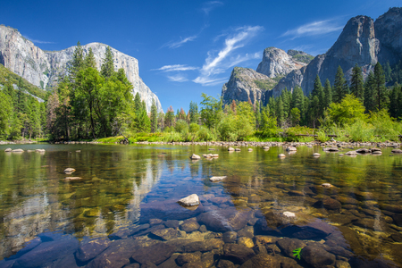 Foto de Classic view of scenic Yosemite Valley with famous El Capitan rock climbing summit and idyllic Merced river on a sunny day with blue sky and clouds in summer, Yosemite National Park, California, USA - Imagen libre de derechos