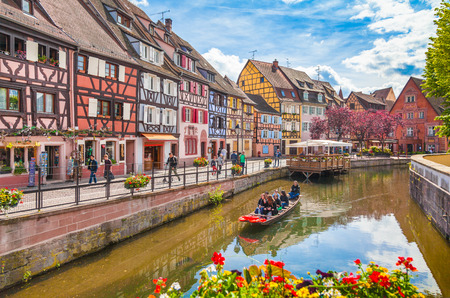 Photo for Beautiful view of the historic town of Colmar, also known as Little Venice, with tourists taking a boat ride along traditional colorful houses on idyllic river Lauch in summer, Colmar, Alsace, France - Royalty Free Image