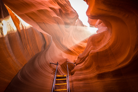 Foto de Beautiful view of amazing sandstone formations with a ladder leading toward a magic light beam in famous Antelope Canyon near the historic town of Page at Lake Powell, American Southwest, Arizona, USA - Imagen libre de derechos