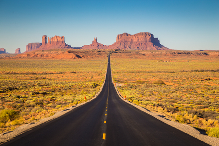 Photo for Classic panorama view of historic U.S. Route 163 running through famous Monument Valley in beautiful golden evening light at sunset on a beautiful sunny day with blue sky in summer, Utah, USA - Royalty Free Image