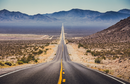 Photo pour Classic panorama view of an endless straight road running through the barren scenery of the American Southwest with extreme heat haze on a beautiful hot sunny day with blue sky in summer - image libre de droit
