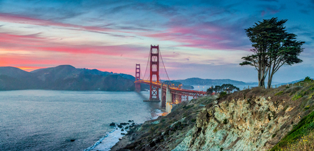 Foto de Classic panorama view of famous Golden Gate Bridge seen from scenic Baker Beach in beautiful post sunset twilight with blue sky and clouds at dusk in summer, San Francisco, California, USA - Imagen libre de derechos