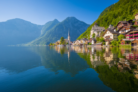 Photo for Classic postcard view of famous Hallstatt lakeside town reflecting in Hallstattersee lake in the Austrian Alps in scenic morning light on a beautiful sunny day in summer, Salzkammergut region, Austria - Royalty Free Image
