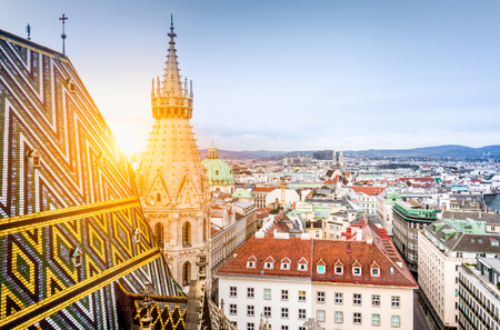 Foto de Aerial view over the historical rooftops of Vienna from the north tower of famous St. Stephen's Cathedral in beautiful golden evening light at sunset in summer, central Vienna, Austria - Imagen libre de derechos